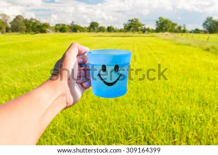 blue plastic cup in hand with blurry rice field background - stock photo