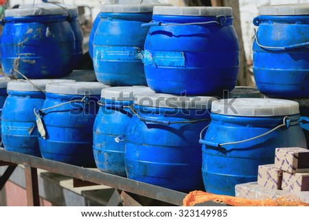 Blue plastic jerrycans containing liquids stacked on shelves in a stall of the market around Tashilhunpo-Heap of Glory monast.-seat of Panchen Lama. Shigatse-Yarlung Tsangpo and Nyang Chu rivers-Tibet - stock photo