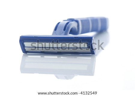 Blue plastic razor with reflection isolated on white. Shallow depth of field with the handle out of focus.