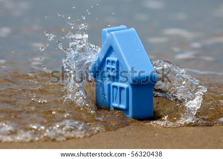 Blue plastic toy house on the sand covered with the waves, forming the spray - a metaphor for the sudden flooding - stock photo