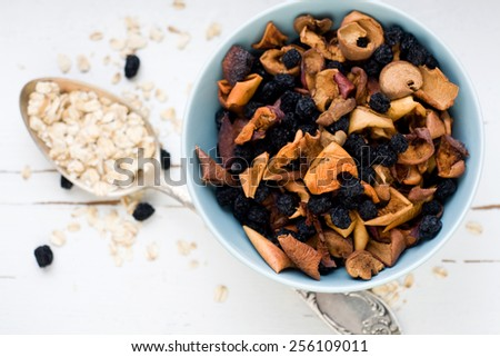 Blue plate with dried apples and berries and a spoon of oatmeal on a white wooden background. Healthy food. - stock photo