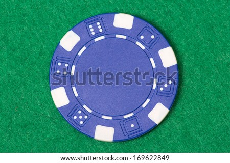 blue poker chip on the green casino table - stock photo