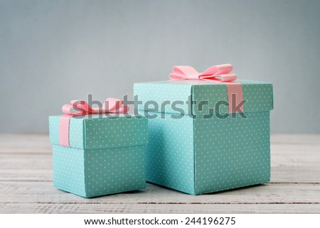Blue polka dots gift boxes with pink ribbons on wooden background - stock photo