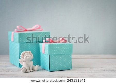 Blue polka dots gift boxes with statuette of angel on wooden background - stock photo