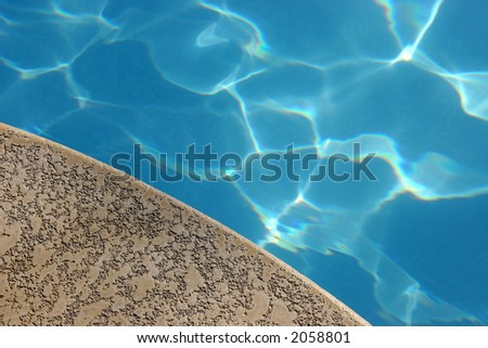 Blue pool water and concrete pool deck. - stock photo