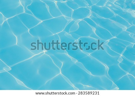 Blue pool water with sun reflections background - stock photo