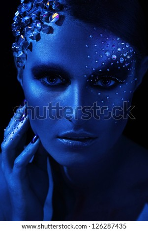 Blue portrait of beautiful woman with artistic make-up - stock photo