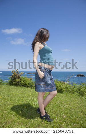 blue pregnant woman on green meadow at Asturian coast - stock photo