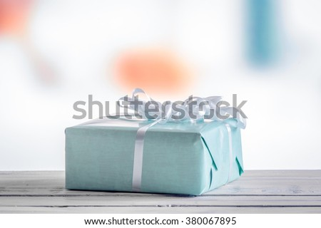 Blue present on a wooden table in daylight - stock photo