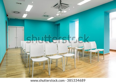 Blue presentation room with white chairs