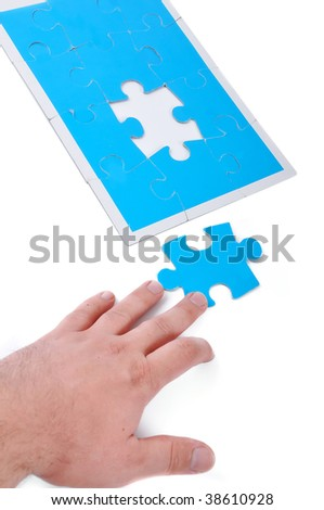 Blue puzzle and hand reaching it