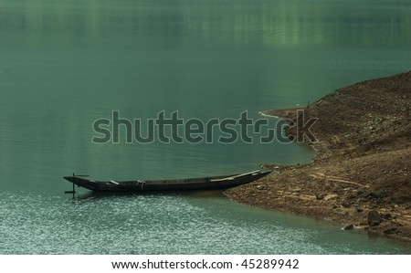 Blue quiet. Moored boat with reflection on the calm water of the lake. - stock photo