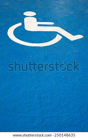 Blue rectangle handicapped sign with wheelchair a cement floor. - stock photo