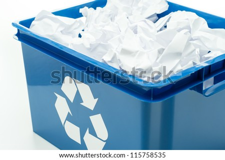 Blue recycling bin box with paper waste on white - stock photo