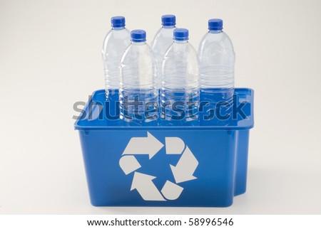 Blue recycling bin full of pet plastic bottles. White background. - stock photo