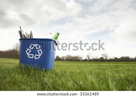 Blue recycling bin sitting on grass - stock photo