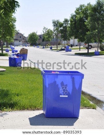 Blue recycling box outside the sidewalk on garbage day - stock photo