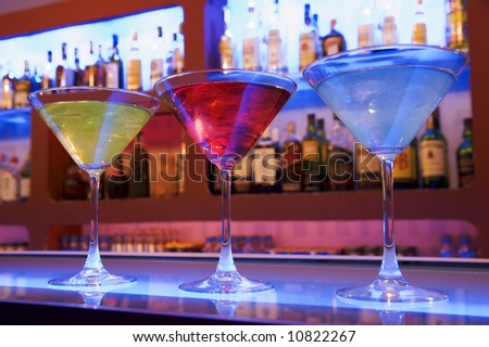 blue, red and yellow cocktail drinks on a bar - stock photo