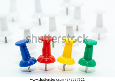Blue,red,yellow and green push pins with white push pins as background.  - stock photo