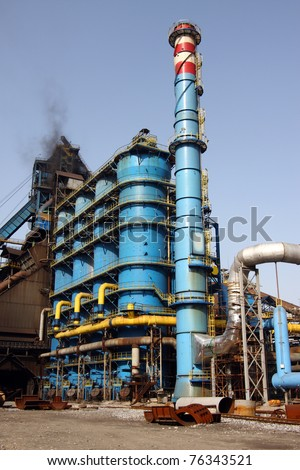 Blue refinery and chimney industrial and chemical site - stock photo