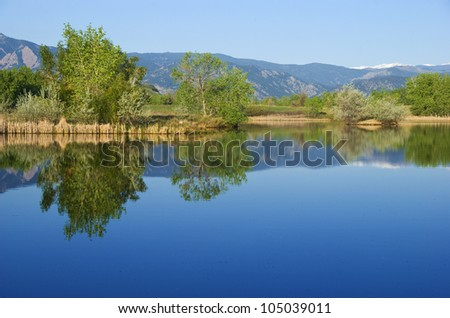 Blue reflections grace a placid lake on the Colorado prairie, with distant view of the Rocky Mountain Continental Divide. - stock photo