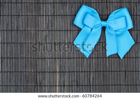 Blue Ribbon on Black Bamboo Setting with Space for Text - stock photo