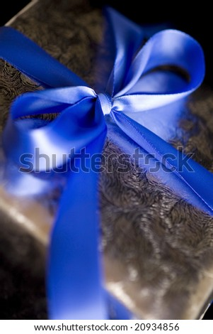 Blue Ribbon Tied in a Bow on Silver Gift.  High Resolution Image Shot with Macro Lens.  Carefully Spotted and Retouched. - stock photo