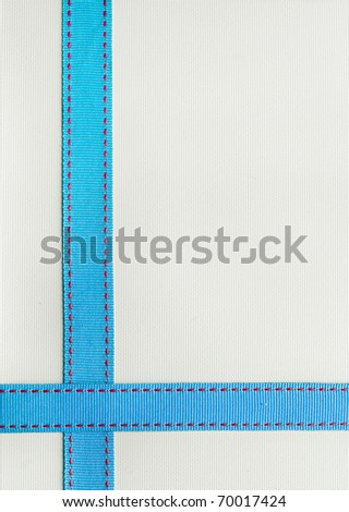 Blue Ribbon with red stitching over a textured background. - stock photo