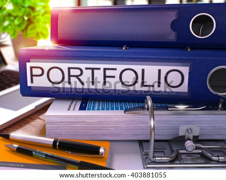 Blue Ring Binder with Inscription Portfolio on Background of Working Table with Office Supplies and Laptop. Portfolio Business Concept on Blurred Background. 3D Render. - stock photo