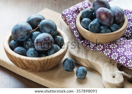 Blue ripe plums in different wooden bowls - stock photo