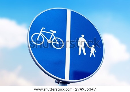 blue road sign for bikes and pedestrians and sunny sky