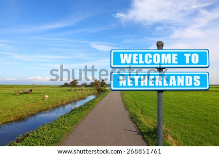 "Blue road sign ""Welcome to Netherlands"" - the invitation to the Netherlands ( visit and travel) against the Dutch meadow landscape  - stock photo"