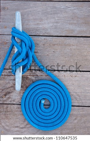 Blue rope coiled on a wooden dock and tied to a metal dock cleat.  Cleats are used for securing docks and lines from boats - stock photo