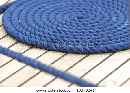 Blue rope on an old rigging boat - stock photo