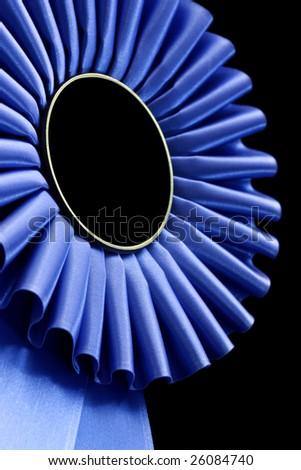 Blue rosette, in closeup, against black background. - stock photo