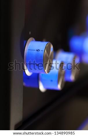 Blue rotary knobs on black panel - stock photo