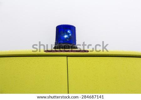 Blue rotating beacon on yellow ambulance car - stock photo