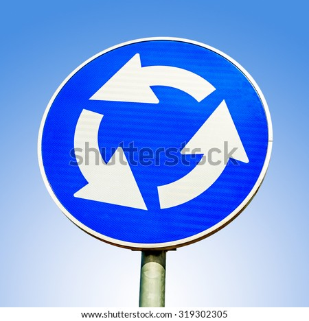 Blue roundabout crossroad road traffic sign against blue background - stock photo