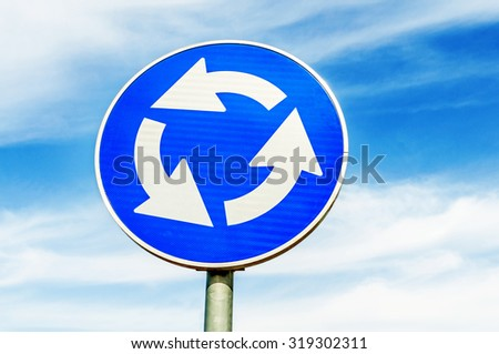 Blue roundabout crossroad road traffic sign against blue sky - stock photo