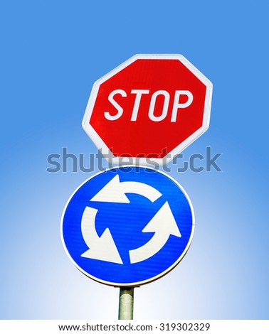 Blue roundabout crossroad road traffic sign with STOP sign against blue cloudy sky - stock photo