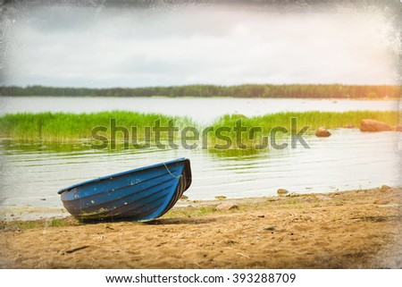 Blue rowing boat stands on a sandy shore in a quiet Bay of the Finnish Gulf. Area for summer camping in the woods. Hamina, Finland, Suomi - stock photo