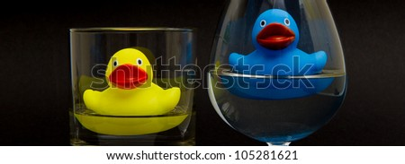 Blue rubber duck in a cognacglass and a yellow one in a whiskyglass - stock photo