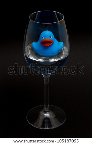 Blue rubber duck in a wineglass with water (black background) - stock photo