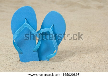 blue rubber flip flops on white sand
