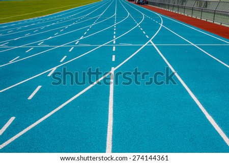 Blue running track at the stadium with white lines