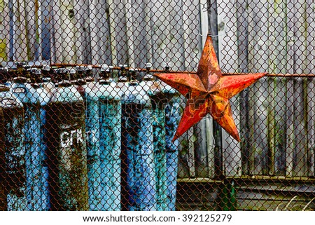 Blue rusty industrial oxygen cylinders in group behind the rusty mesh fence with rusty red soviet star. Old Iron soviet red star on the rusty mesh fence background. Chernobyl Territory of Chernobyl-2 - stock photo