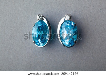 blue sapphire earrings on grey background - stock photo