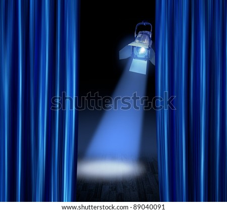 Blue satin curtains reveal stage spotlight lamp beam - stock photo