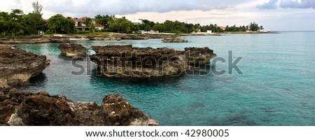 Blue sea and coral rocks with sky background - stock photo