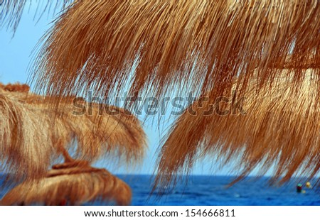 blue sea between natural orange straw sunshades on beach at summer resort - stock photo